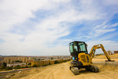 Digger at Rest Overlooking City. Small digger rests in open space above city center, where a new housing complex will be situated royalty free stock photos