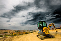 Digger at Rest Overlooking Stormy City. Small digger rests in open space above city center, where a new housing complex will be situated Stock Image