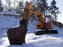 Digger in snow. Heavy digger covered in snow. Construction work stopped by winter stock photography