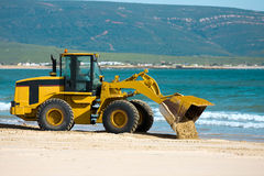 Digger Tipping Sand on Coastline. Articulated Digger clears sand on beach in Spain. Mountains in background. Sea and sand Stock Images