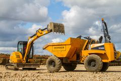 A digger tipping soil into a site dumper truck Royalty Free Stock Photos