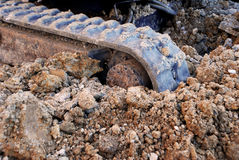 Digger tracks running through soil and stones Royalty Free Stock Image