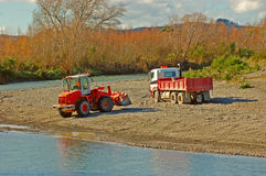Digger and truck. A digger and a truck collecting gravel for roading from river shore Royalty Free Stock Photos