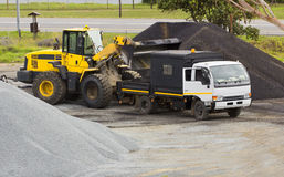 Digger and truck working with gravel stock images