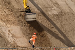 Digger works at new road construction site Stock Image