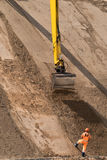 Digger works at new road construction site. Digger works at new highway construction site Royalty Free Stock Photo