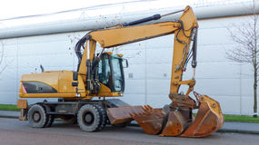 Digger. Yellow digger parked side view Stock Image