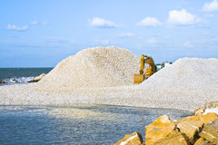 Diggers on the seashore. Building a breakwater Royalty Free Stock Photos