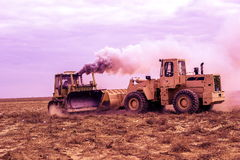 Diggers in the steppe Betpakdala. Wheeled and tracked diggers argue who is stronger Stock Images