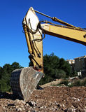 Digging. Shovel from an excavator machine digging on the soil royalty free stock image