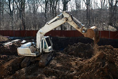 Digging. A excavator digging the base of a new building stock images