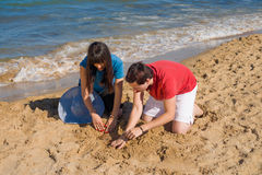 Digging on the beach Stock Photography