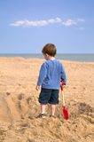 Digging a hole. Toddler on the beach admiring a huge hole he has just dug in the sand stock photo