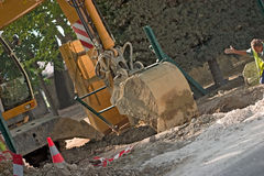 Digging the hole. Back-hoe being guided by a worker down into the ground Stock Photos