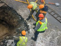 Digging a hole to eliminate the leakage of pipes in the middle of winter. A group of road workers from public utilities in reflective special vests are royalty free stock images