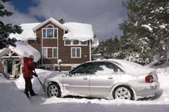 Digging Out. A couple digging out their car after a major snowfall stock image