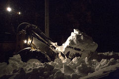 Digging out. Affects on Alden, NY of a lake affect snowstorm coming off Lake Erie in Western New York. Approximately 18:00 on 19 November 2014. Front end loader stock photography