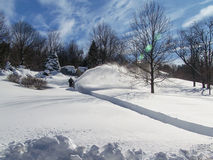 Digging Out After a Blizzard - Snowthrower. Man using snow blower to clear very long driveway.  Beautiful background.  Large field of virgin snow Royalty Free Stock Photography
