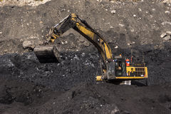 Digging out the coal. 40 ton digger removes high grade coal from a seam at an open cast coal mine on August 31, 2013 near Westport, New Zealand stock photo