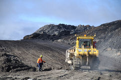 Digging out the coal. WESTPORT, NEW ZEALAND, AUGUST 31, 2013: Coal mine worker passes a dozer at Stockton Coal Mine, Westland, New Zealand Stock Photos