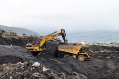 Digging out the coal. WESTPORT, NEW ZEALAND, MARCH 4, 2015: 40 ton digger removes high grade coal from a seam at an open cast coal mine on March 4, 2015 near Royalty Free Stock Photos