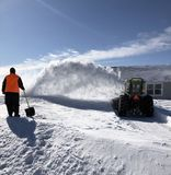Digging out from a snowstorm. Big snowblower on a tractor blows out the snow from a blizzard stock photos
