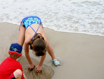 Digging in the Sand. 2 children at beach Royalty Free Stock Photos