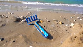 Digging toy on sand near beach stock footage