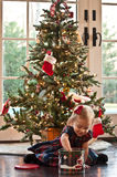 Digging for Treasure. Little Girl Opening A Cookie Tin In Front Of The Christmas Tree Stock Photo