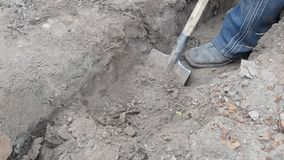 Digging a trench in grey dry soil with a spade. Closeup of digging a trench in grey dry soil with a spade stock footage