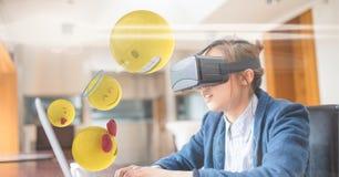 Digitaal geproduceerd beeld van emojis die door zakenman vliegen die VR-glazen dragen terwijl het gebruiken van laptop bij D stock foto