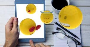 Digitaal geproduceerd beeld van emojis die over hand vliegen die tabletcomputer met behulp van door kop bij lijst stock illustratie