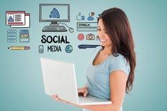 Digitaal geproduceerd beeld van vrouw die laptop met diverse pictogrammen op blauwe achtergrond met behulp van Royalty-vrije Stock Foto's