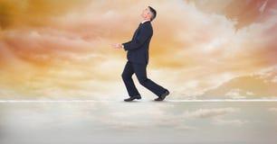 Digitaal samengesteld beeld van zakenman het in evenwicht brengen op kabel royalty-vrije stock afbeelding