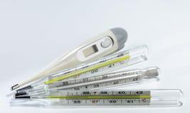 Digitaces y termómetros médicos del mercurio en fondo neutral fotos de archivo