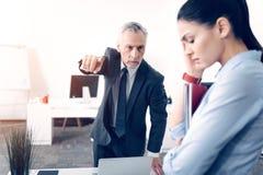 Digitación masculina frustrada del jefe en la puerta mientras que oficinista de leña imagenes de archivo