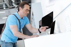 Digitación sorprendente del hombre hacia el ordenador portátil en la tienda fotos de archivo