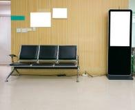 Digital affischtavlamellanrum med stol på wood bakgrund Royaltyfria Bilder