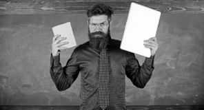 Digital against paper. Teacher bearded hipster holds book and laptop. What would you prefer. Teacher choosing modern. Teaching approach. Choose right teaching stock images