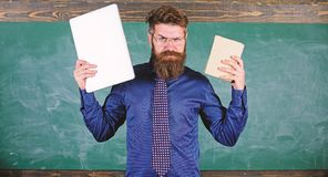 Digital against paper. Teacher bearded hipster holds book and laptop. What would you prefer. Teacher choosing modern. Teaching approach. Choose right teaching royalty free stock photography