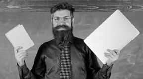 Digital against paper. Teacher bearded hipster holds book and laptop. What would you prefer. Teacher choosing modern. Teaching approach. Paper book against stock image