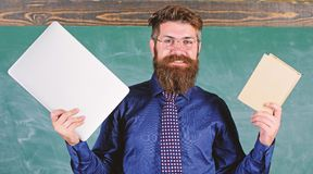 Digital against paper. Teacher bearded hipster holds book and laptop. What would you prefer. Teacher choosing modern. Teaching approach. Paper book against stock photos