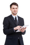 Digital age businessman. Confident young man in formalwear working on digital tablet and smiling while standing isolated on white stock image
