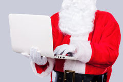 Digital age Santa. Santa Claus working on laptop while standing against grey background royalty free stock image