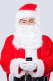 Digital age Santa. Traditional Santa Claus holding mobile phone while standing against grey background stock image
