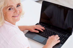 Digital age senior. Top view of cheerful senior woman looking at camera and smiling while working on laptop royalty free stock photos