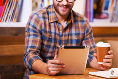 Digital age student. Close-up of cheerful young man holding coffee cup and looking at his digital tablet while sitting at the desk with bookshelf in the stock photo