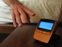Digital alarm clock. Man waking up and snoozing the alarm Royalty Free Stock Photos