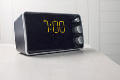 Digital alarm clock with  digits showing seven oclock. Digital alarm clock with yellow digits showing seven oclock Stock Photos
