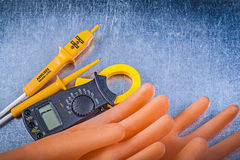 Digital ammeter electric tester dielectric rubber gloves on meta Royalty Free Stock Photo